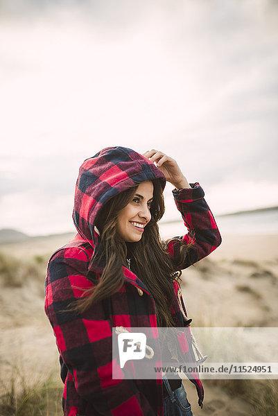 Lächelnde junge Frau mit langen braunen Haaren in Kapuzenjacke am Strand
