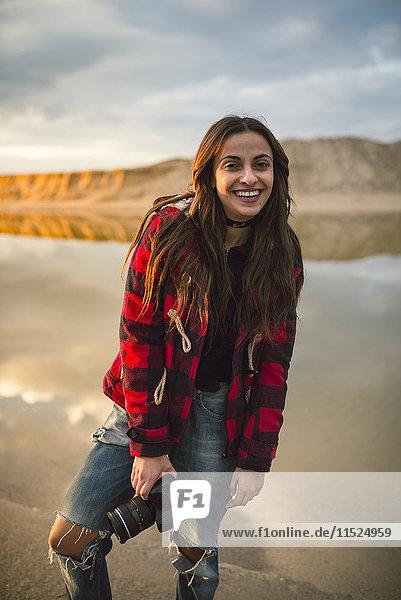 Porträt einer lächelnden jungen Frau mit Kamera am Strand