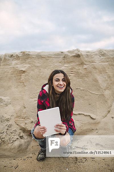 Porträt einer lächelnden jungen Frau mit am Strand kauernder Tafel
