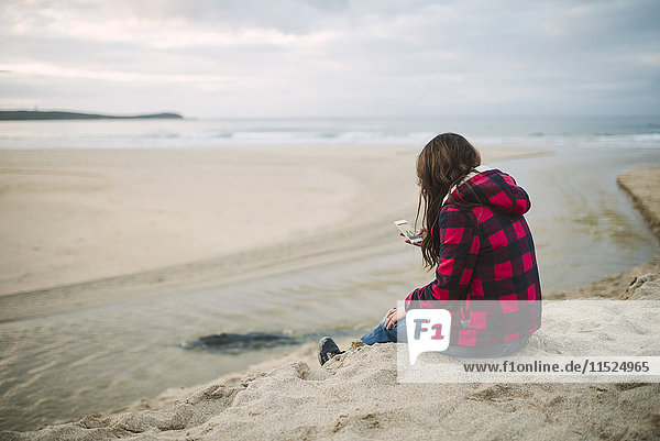 Young woman on the beach looking at cell phone