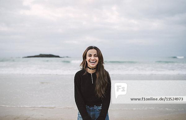 Porträt einer lachenden jungen Frau am Strand