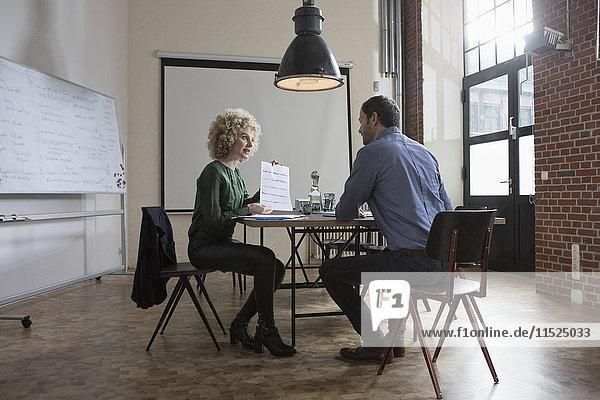 Mann und Frau diskutieren über Papier im Sitzungssaal