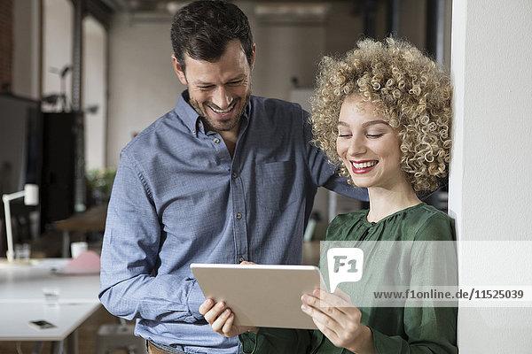 Lächelnder Mann und Frau beim Betrachten der Tablette im Büro