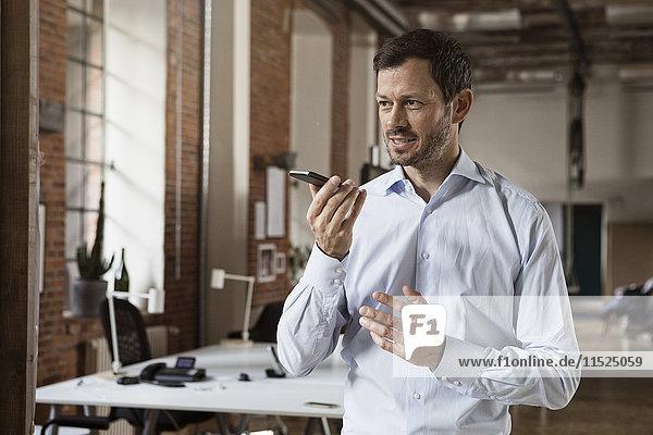 Geschäftsmann mit Handy im Büro