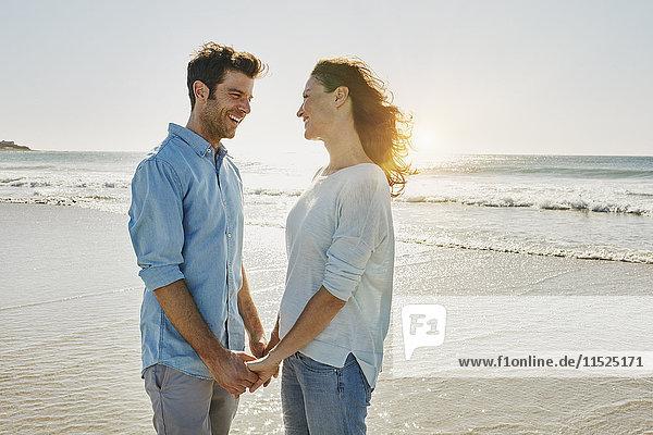 Ein glückliches Paar hält sich am Strand an den Händen.