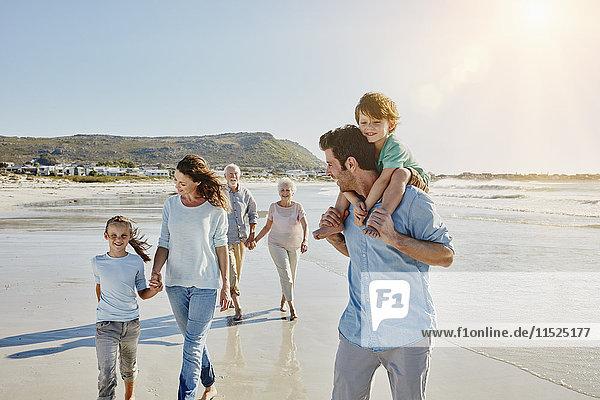 Drei Generationen Familienbummel am Strand