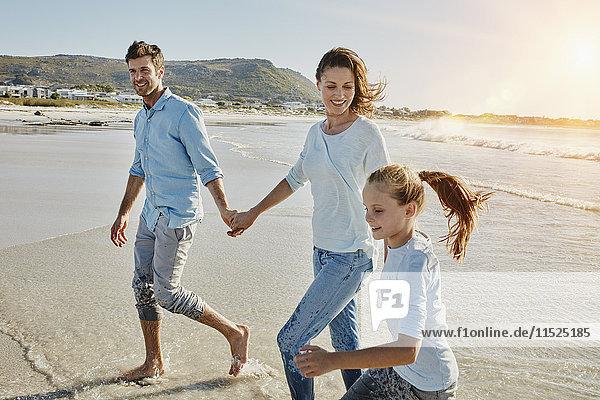 Paar Spaziergänge mit Tochter am Strand