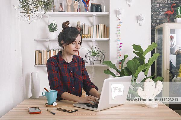 Junge Frau mit Laptop zu Hause