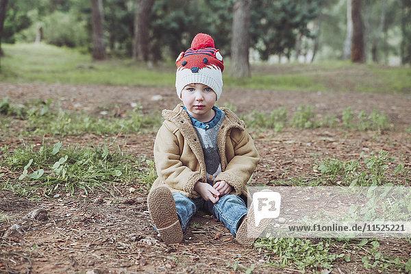 Portrait of boy wearing wooly hat sitting inforest