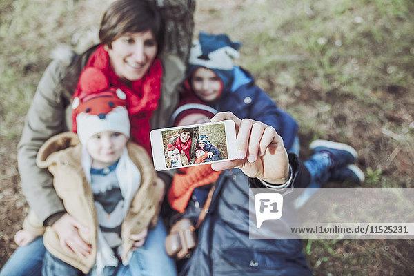 Familie  die ein Selfie mit Smartphone im Wald nimmt
