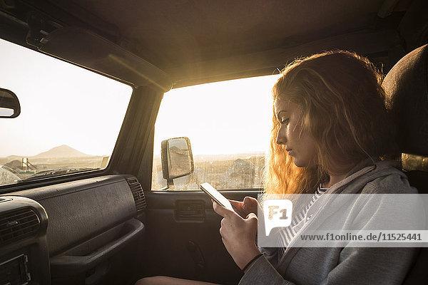 Frau im Auto schaut auf Handy