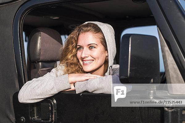 Porträt einer glücklichen jungen Frau  die sich aus dem Autofenster lehnt.