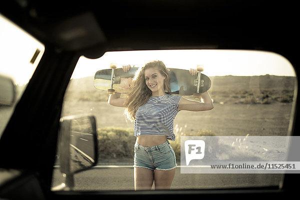 Spanien  Teneriffa  junge Frau mit Skateboard durchs Autofenster gesehen Spanien, Teneriffa, junge Frau mit Skateboard durchs Autofenster gesehen