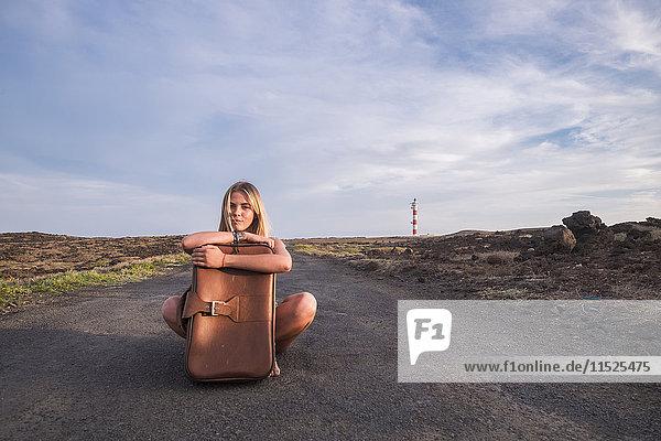 Spanien  Teneriffa  junge blonde Frau auf leerer Straße sitzend mit Koffer Spanien, Teneriffa, junge blonde Frau auf leerer Straße sitzend mit Koffer