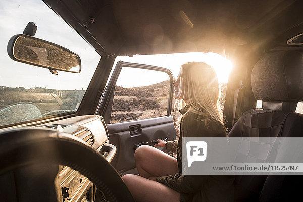 Frau steigt bei Sonnenuntergang ins Auto Frau steigt bei Sonnenuntergang ins Auto