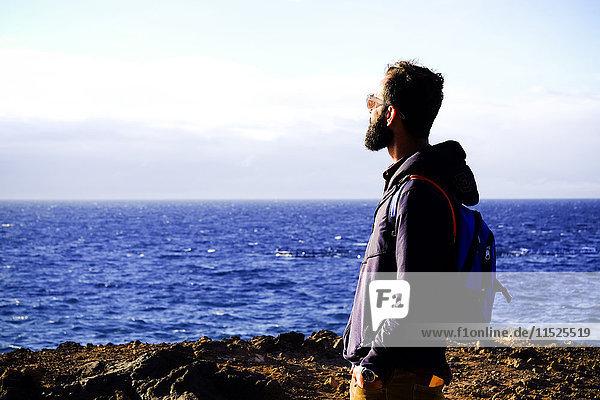 Mann mit Rucksack mit Blick aufs Meer