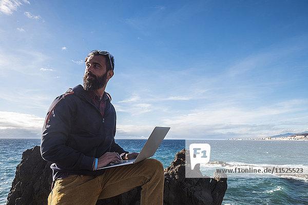 Spanien  Teneriffa  Portrait eines Mannes mit Laptop vor dem Meer