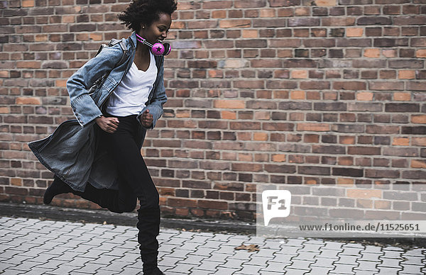 Smiling young woman with headphones and backpack running on pavement