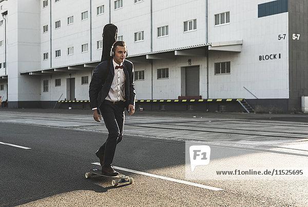 Junger Mann mit Gitarrenkoffer beim Skateboardfahren auf der Straße