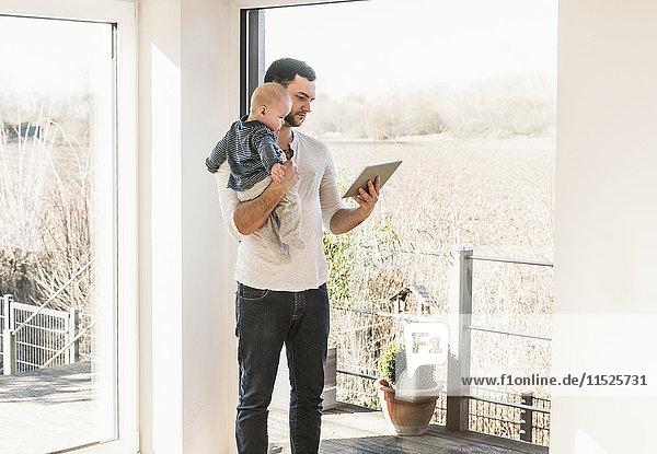 Vater steht zu Hause  trägt Baby-Sohn und liest Textnachrichten