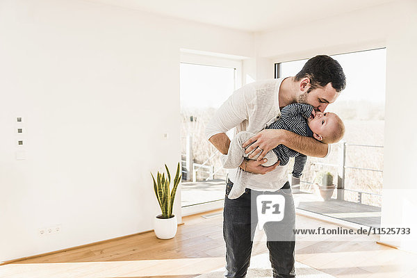 Father holding and hugging his baby son  standing in comfortable home