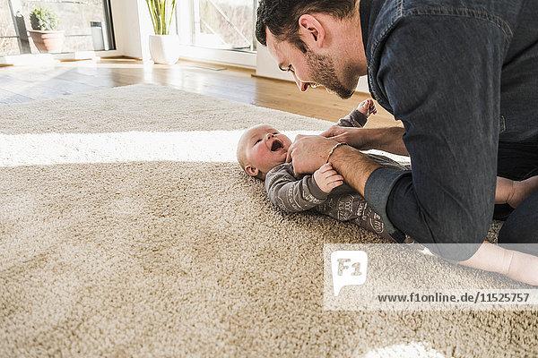 Vater und Sohn spielen zu Hause auf dem Teppich.