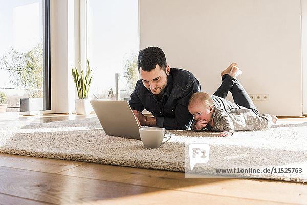 Vater mit Baby-Sohn mit Laptop auf Teppich liegend