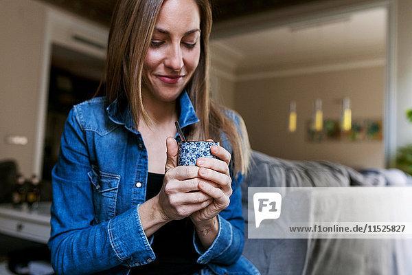 Junge Frau genießt eine Tasse Kaffee zu Hause