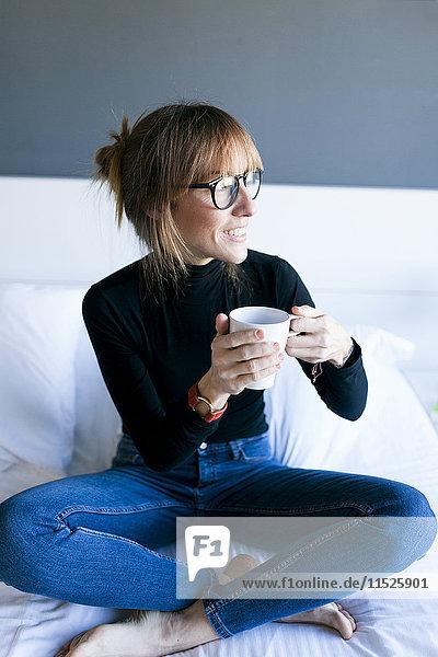 Junge Frau sitzt auf dem Bett und trinkt eine Tasse Kaffee.