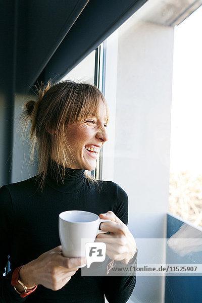 Glückliche junge Frau zu Hause trinkt eine Tasse Kaffee und schaut aus dem Fenster.
