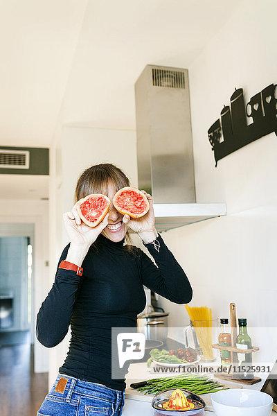 Junge Frau  die Grapefruitsaft auspresst Junge Frau, die Grapefruitsaft auspresst