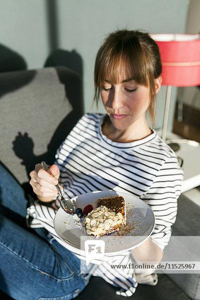 Junge Frau isst ein Stück veganen Kuchen.