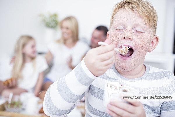 Junge isst aus Müslischale mit Familie im Hintergrund