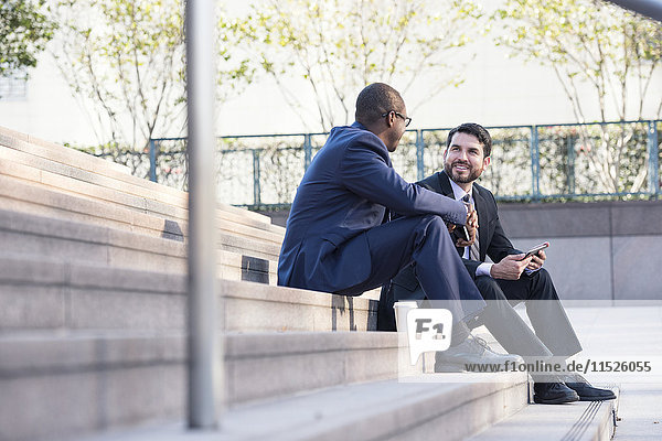 Two businessmen sitting on stairs talking