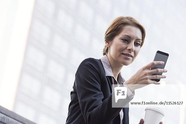 Lächelnde Geschäftsfrau mit Handy und Kaffee zum Mitnehmen