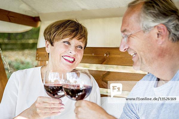Happy senior couple clinking red wine glasses