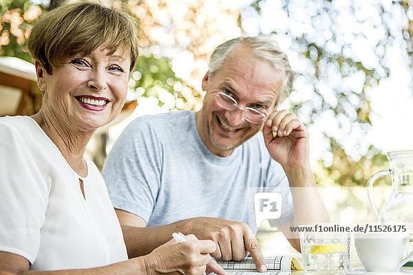 Lächelndes Seniorenpaar im Freien beim gemeinsamen Kreuzworträtselspiel