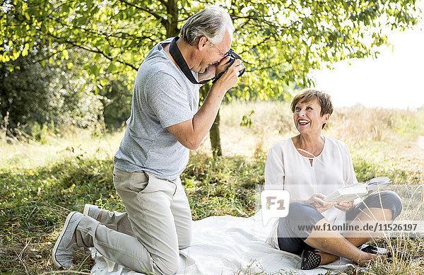 Glücklicher älterer Mann fotografiert seine Frau auf der Wiese