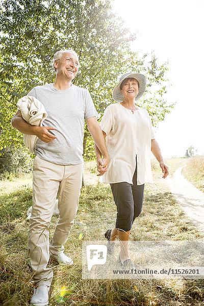 Glückliches Seniorenpaar beim Wandern mit Decke in der Natur