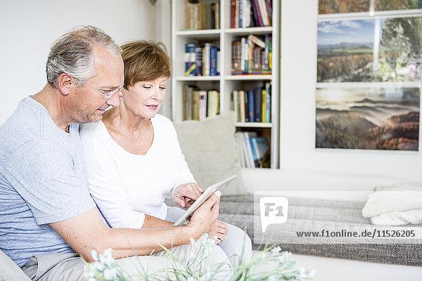 Seniorenpaar zu Hause auf der Couch sitzend mit digitalem Tablett