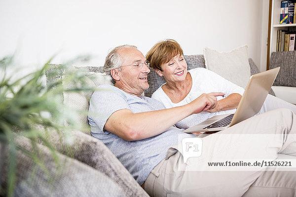 Seniorenpaar zu Hause sitzend auf der Couch mit Laptop