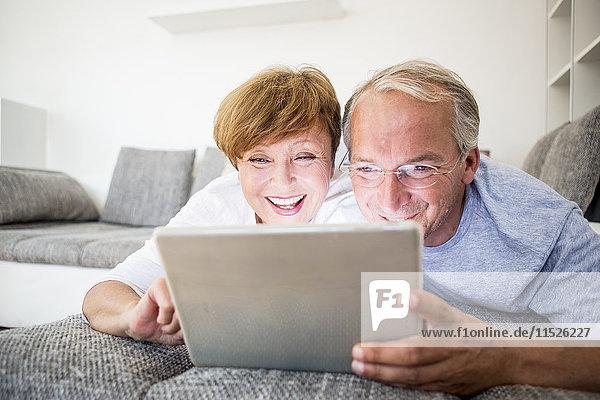 Glückliches Seniorenpaar zu Hause auf der Couch liegend mit digitalem Tablett