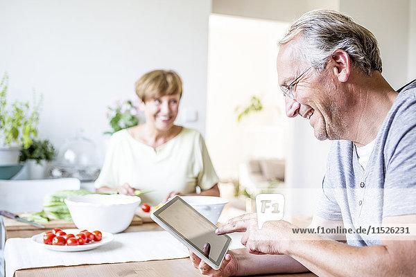 Senior Mann zu Hause mit digitaler Tablette und Frau  die im Hintergrund Salat zubereitet.
