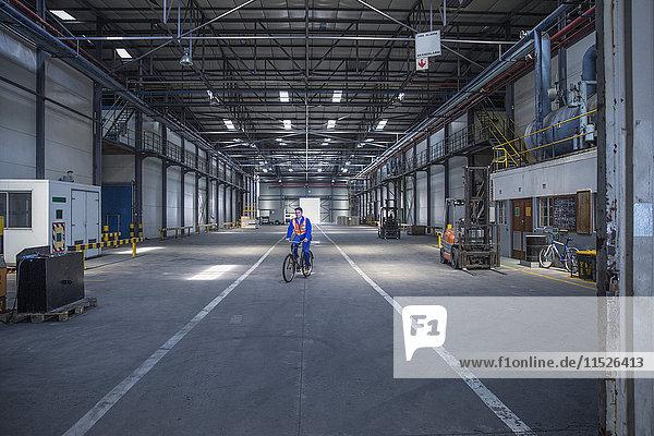 Arbeiter auf dem Fahrrad im Lagerhaus