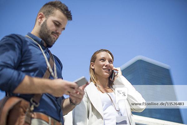 Junger Mann und Frau  die Mobiltelefone im Freien benutzen