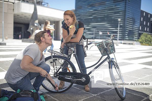 Mann hilft Frau beim Aufpumpen ihres Fahrradreifens in der Stadt