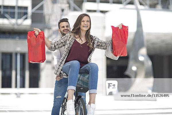 Fröhliches junges Paar beim Fahrradfahren in der Stadt mit Einkaufstaschen