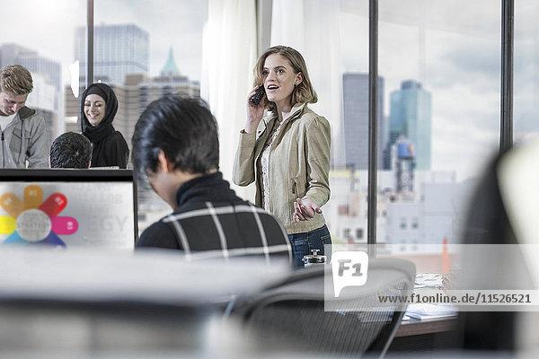 Frau am Telefon im geschäftigen Büro