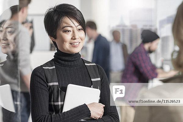 Porträt einer lächelnden Frau mit einer Tablette im Amt