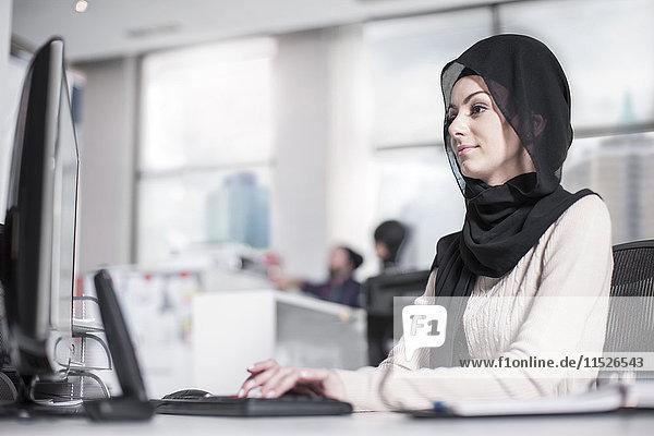 Junge Frau mit Hijab auf dem Schreibtisch im Büro